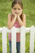 sad little girl leaning on fence