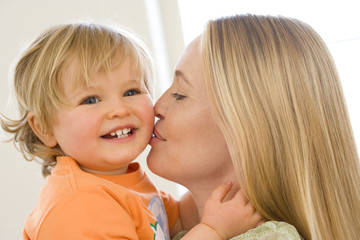 Potrait of mother and smiling toddler indoors.