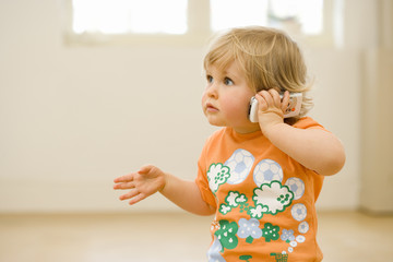 Toddler indoors talking on mobile phone.