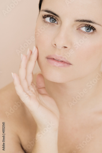 Portrait of young woman touching her cheek