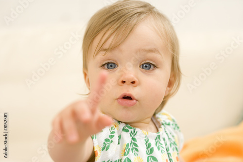 Baby girl (9-12 months) pointing, portrait, close-up (differential focus)