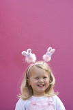 Girl (2-4) wearing bunny rabbit headband by pink wall, smiling, portrait