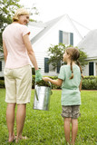 mother and daughter carrying watering can