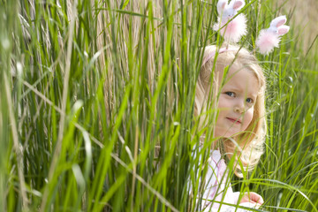 Girl (2-4) in bunny rabbit headband hiding in long grass, side view