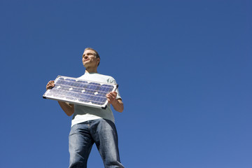 Man with solar panel, smiling, low angle view