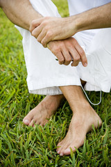 cropped image man's legs and bare feet on grass