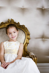 Little girl sitting in an ornate chair wearing a party dress