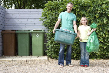 Father and daughter (9-11) in driveway with recycling, smiling, portrait