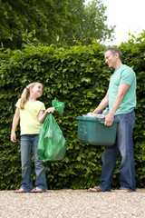 Father and daughter (9-11) with recycling by hedge, smiling at each other