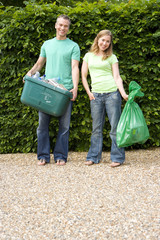 30's couple outdoors against green hedge holding recycling box and bag .