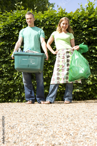 Young couple by hedge outdoors, man with recycling bin, woman with plastic bag, portrait, ground view