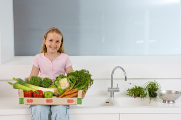 Girl (4-6) sitting on side in kitchen with box of vegetables on lap, smiling, portrait