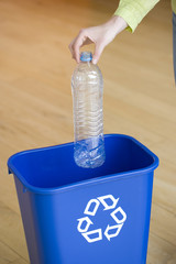 Man putting bottle into recycling bin, close-up of hand