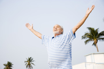Portrait of a senior man standing on a beach with arms outstretched