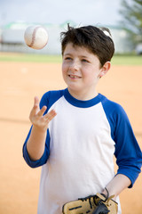 Boy throwing baseball in air
