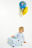 Baby boy (6-9 months) with baloons and present