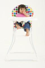 Baby girl (3-6 months) in highchair, portrait