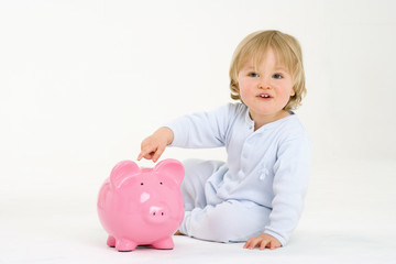 Baby boy (6-9 months) playing with piggy bank, smiling