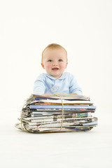 Baby boy (3-6 months) by bundle of newspapers, smiling