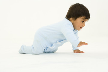 Baby boy (3-6 months) crawling, side view