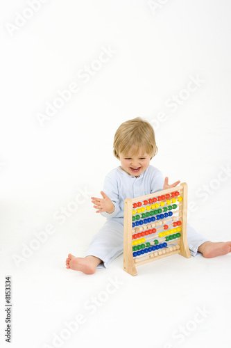 Baby boy (6-9 months) playing with abacus, smiling