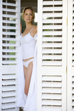 Young woman in underwear and bathrobe looking out of shutters