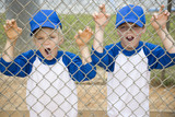 two boys roaring like lions through fence at baseball pitch