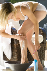 Young woman shaving legs in basin outdoors, low angle view