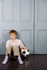 little boy sitting on floor with football