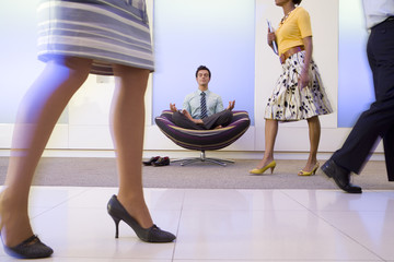 Businessman meditating in chair in office foyer, colleagues walking past, low section (blurred motion)