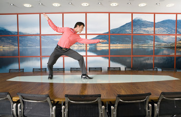 Businessman pretending to surf on boardroom table, side view