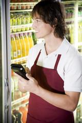 Shop assistant stocktaking in a supermarket