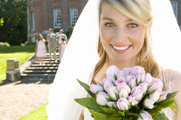 Bride holding up bouquet of flowers, smiling, portrait, close-up