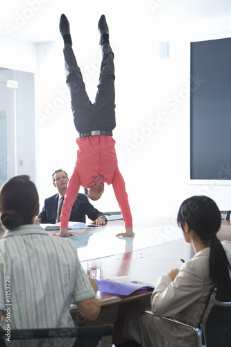 20's businessman doing handstand on board desk in meeting room watched by colleagues.