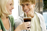 Young couple sharing a cola drink in a diner