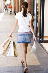 Rear view of woman with shopping bags walking down the street