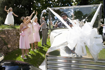 Bridal party waving to bride and groom in vintage car wrapped in bow