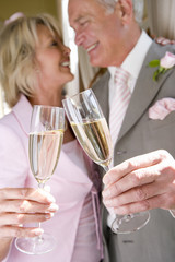 Senior bride and groom toasting with champagne flutes, close-up of glasses, low angle view