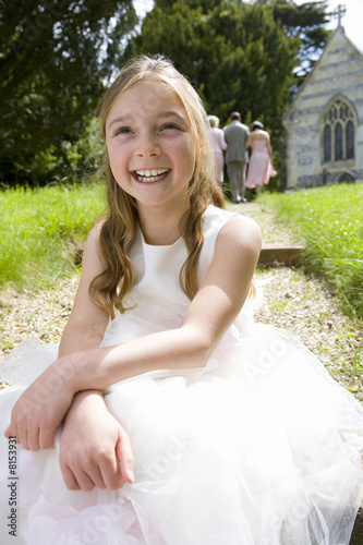 Flower girl (10-12) on path by church, smiling, close-up, low angle view
