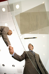 Two businessmen shaking hands by paperwork and pen on glass table, low angle view through glass