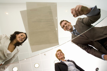 Businessman by two businesswomen preparing to sign paperwork on glass table, smiling, low angle view through glass