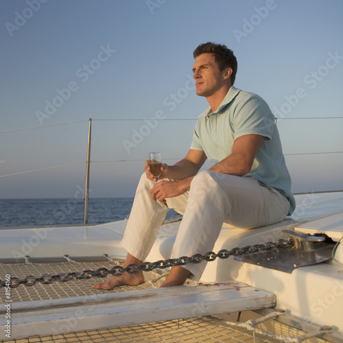 A man relaxing with a drink on a boat