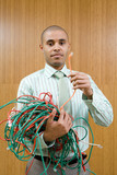 Businessman with bunch of tangled cable leads, holding one up, portrait