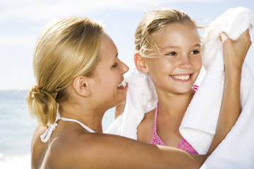 A mother drying her daughter with a  towel on the beach