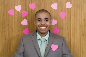 Businessman by wall covered in heart shaped decorations, one on jacket, smiling, portrait, close-up