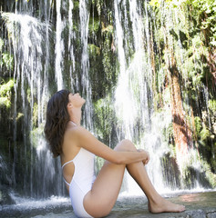 A woman sitting by a waterfall