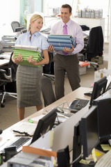 Businessman and woman carrying folders in office, smiling at each other, elevated view