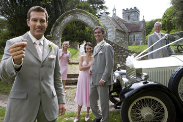 Groom holding out ring by vintage car and wedding party, church in background, smiling, portrait