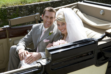 Bride and groom in back of convertible vintage car, smiling, portrait, elevated view