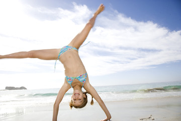A young girl cartwheeling on the beach